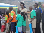 "Rwanda's First Lady Jeannette Kagame, U.S. Ambassador to Rwanda Don Koran, and other dignitaries hand out awards to Rwandan schoolchildren who distinguished themselves during Rwanda's annual ""Reading Week."""